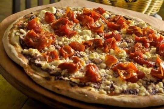 A pizza Mediterrâneo é feita com finas fatias de berinjela, tomate seco picadinho e ricota regada ao pesto de azeitona preta