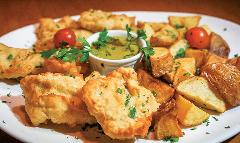 Merluza à milanesa acompanhada de batatas assadas e molho de alcaparras