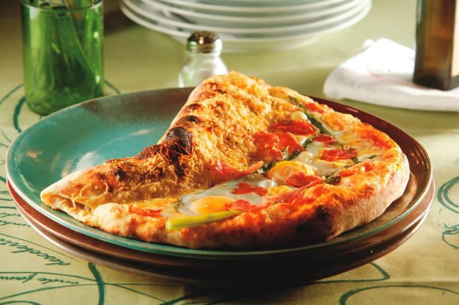 Exclusividade da Bráz Quintal: a carola traz meia pizza coberta por mussarelas bovina e de búfala mais tomate-cereja e rúcula e meio calzone recheado de linguiça artesanal