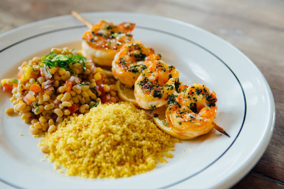 Espetinho de camarão: feito na brasa, acompanha salada de feijão-manteiguinha e um mix de farinhas de milho, pão e biscoito de polvilho