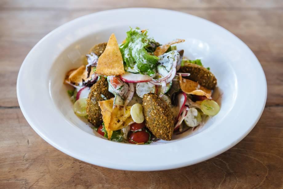 Faláfel: servido sobre salada de folhas, rabanete, pepino, cebola-roxa, uva e torrada ao molho de iogurte
