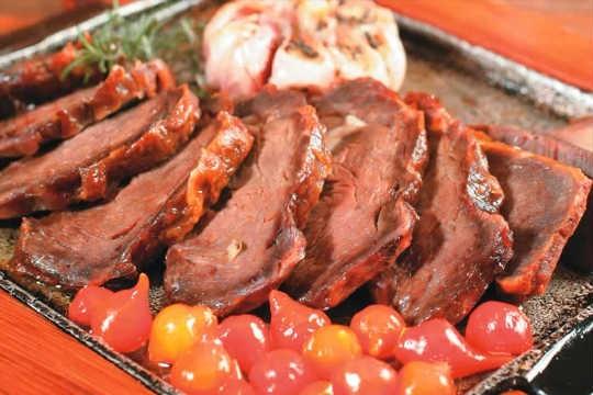Uma das campeãs de pedidos do brasileiro Mocotó: carne de sol na chapa com alho assado, pimenta-biquinho e chips de mandioca