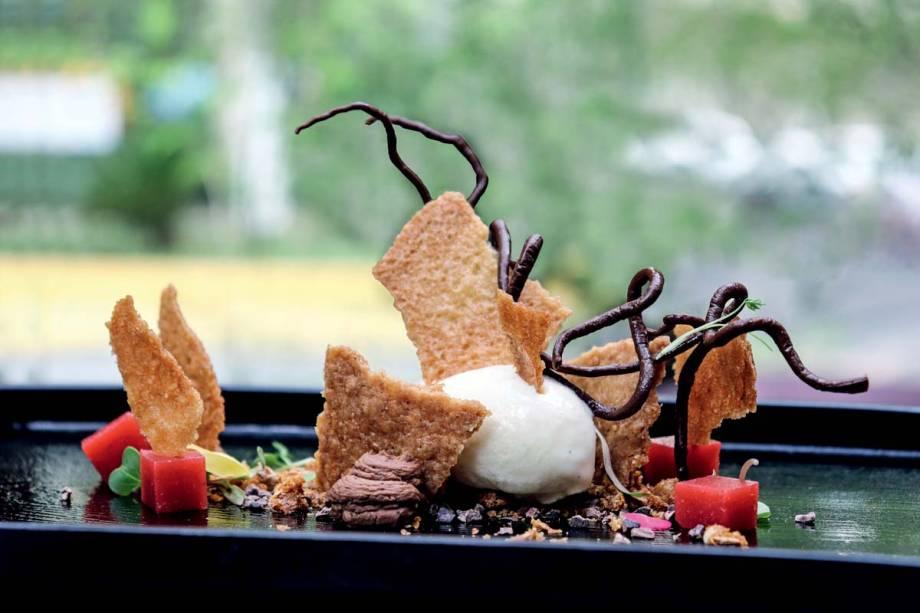 Chocolate em diferentes texturas com uma placa de praliné e servidas junto de sorvete de baunilha mais cubos de gelatina de morango fresco