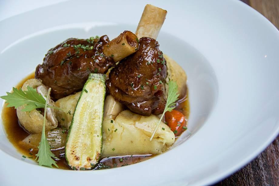 Stinco de cordeiro, vem com um mix de legumes, purê de batata e cogumelo shiitake empanado e crocante