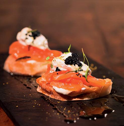 Tapas de salmão defumado servidas sobre fatia de pão ciabatta