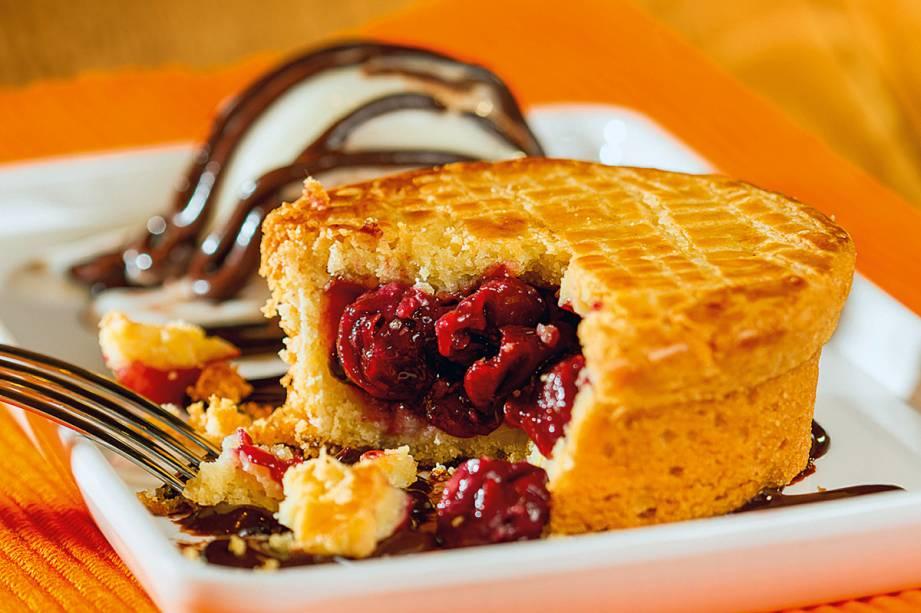 Tortinha de cereja com uma bola de gelado de creme e calda de chocolate
