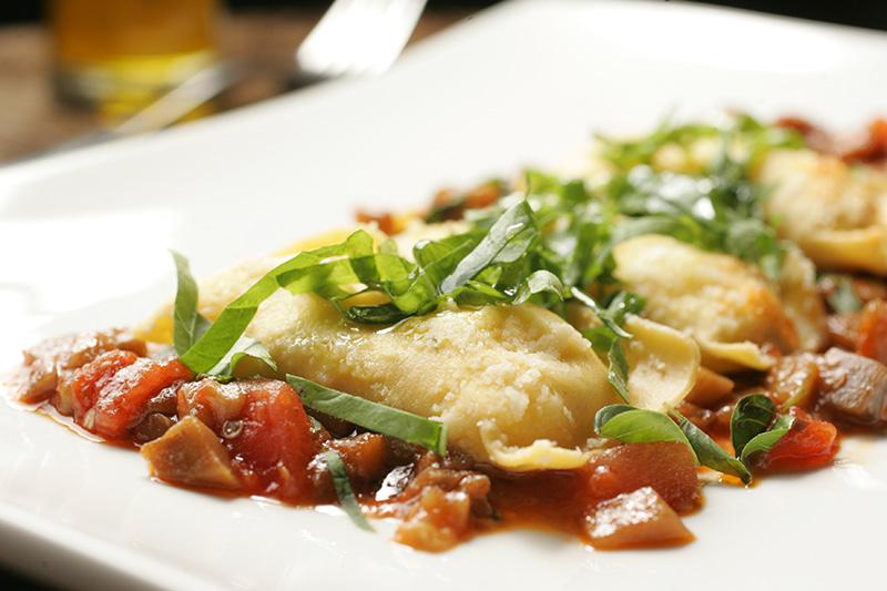 Torteloni de burrata com tomate San Marzano, ragu de beringela e rúcula