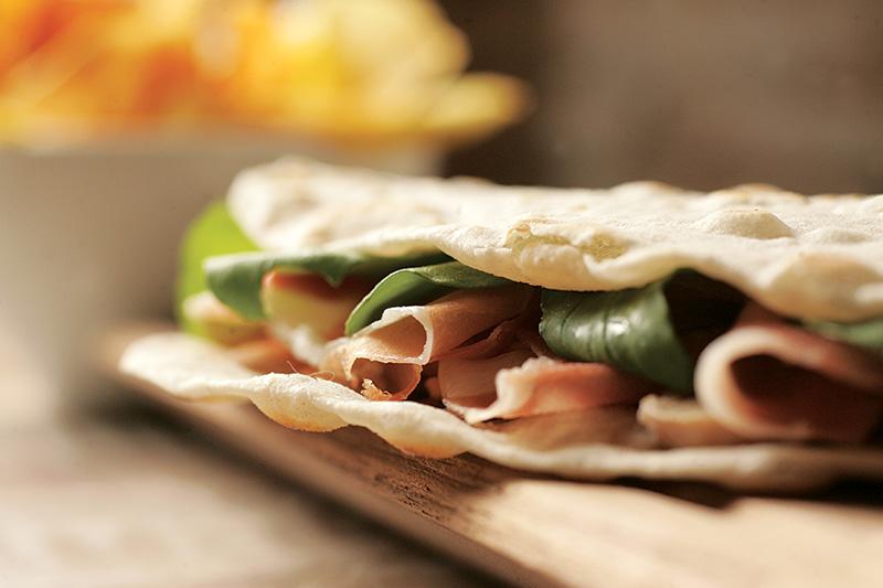 Piadina de presunto cru, lascas de queijo grana padano, cogumelo-de-paris e rúcula