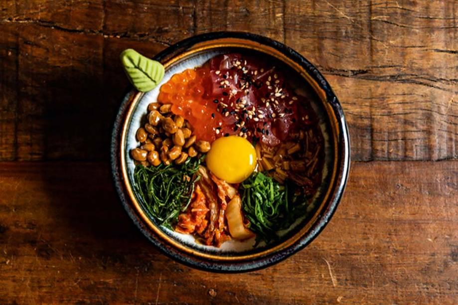 O yamakake, com base de cará ralado, ganha a cobertura de atum cru em pedacinhos, soja e acelga fermentadas, ovas de salmão, cebolinha, cogumelo em conserva, shissô e gema de ovo de codorna