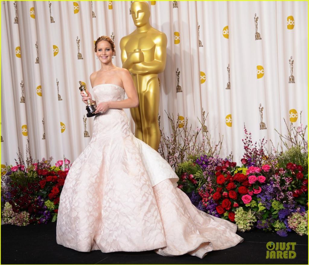 """Jennifer Lawrence veste Dior Couture no Oscar de 2013 No ano passado foi o vestido sob medida da Dior que deixou todo mundo de queixo caído. Cortado na cintura e com caimento perfeito dos quadris para baixo. Como se o cauda de mais de um metro não fosse o drama o suficiente para uma noite, J-Law, """"abraçou"""" as escadas quando foi receber seu prêmio de melhor atriz. Aparentemente, ainda não superamos este momento! oluptuoso Dior que Raff Simons creó para Jennifer Lawrence, vestido que le jugará una mala pasada al subir al escenario a recoger su primer Oscar. El tropiezo que hizo historia.  (Foto: Reprodução)"""