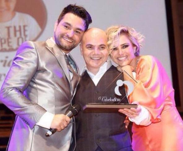 Adriano Oliveira, ao centro, recebe prêmio de André Sartori e Nathália Rodrigues (Foto: Reprodução/Instagram)