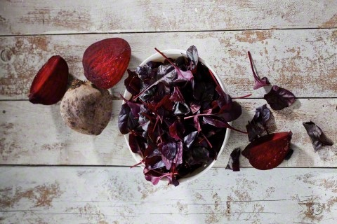 Beetroot and bowl of leaves on wood