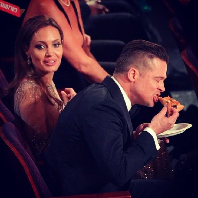 Brad Pitt traçando uma pizza ao lado de Angelina Jolie
