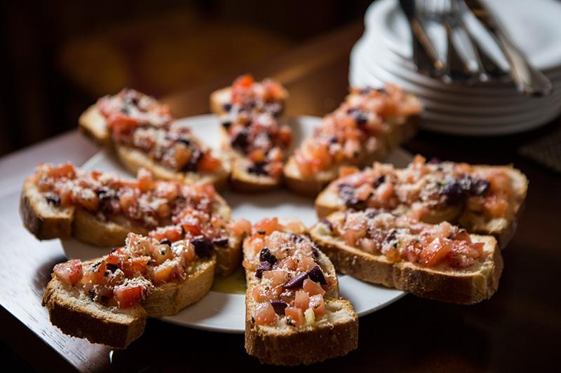 Montadas sobre um pão macio, a porção de enormes bruschettas traz tomate picado, azeitona preta e parmesão