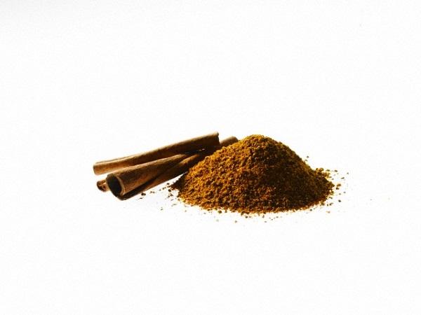 Studio shot of Ground Cinnamon and Cinnamon Sticks on white background