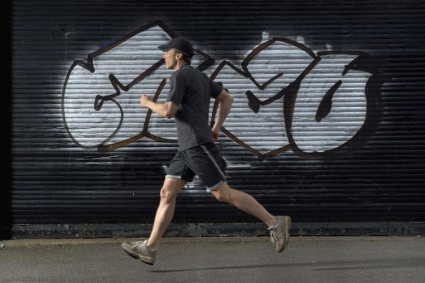 man running past graffitti