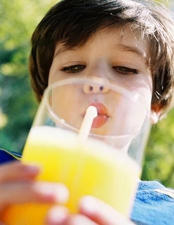 Boy drinking glass of orange juice with straw