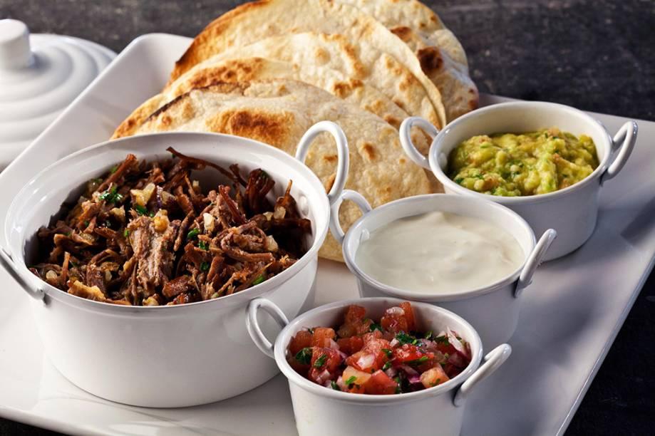 Fajitas mexicanas para serem montadas na mesa vêm com carne desfiada, sour cream, guacamole e salsa pico de galo