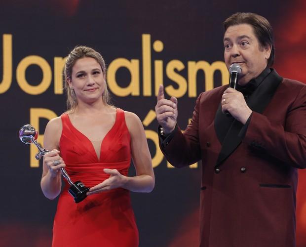 A jornalista Fernanda Gentil recebe prêmio do apresentador Fausto Silva