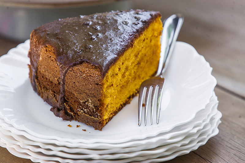 O bolo de cenoura é servido em fatia alta com cobertura de chocolate