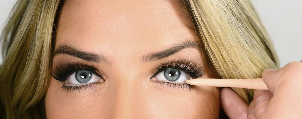 Após delinear a parte superior dos olhos aplique um lápis bege por toda linha d'água, ou seja, na parte inferior dos olhos. A aplicação do lápis claro dá um efeito de olhos maiores.