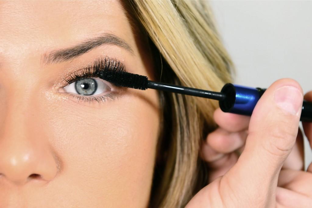 Aplique máscara para cílios preta em toda a extensão dos olhos. Ela vai unir os cílios naturais aos postiços. Aplique também nos cílios inferiores.