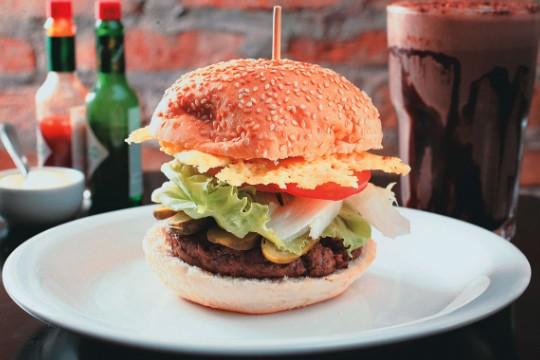 Hambúrguer artesanal: ladeado por picles, alface, tomate e disco de parmesão crocante