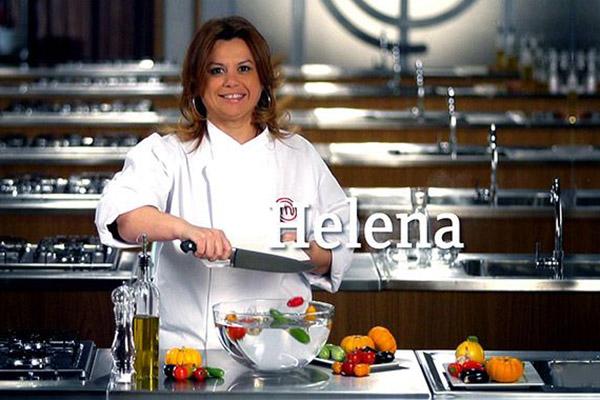 Helena Manosso sorrindo atrás de bancada do MasterChef enquanto despeja legumes cortados de tábua para tigela de vidro.