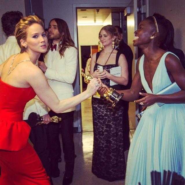 Jennifer Lawrence, que concorria por Trapaça, tentando agarrar o Oscar da vencedora Lupita