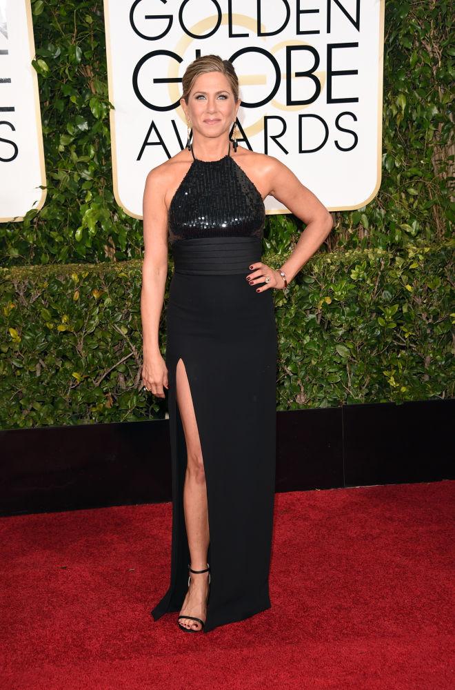 Jennifer Aniston, com vestido preto Saint Laurent, escolheu a fenda para chamar atenção durante o red carpet (Foto: Reprodução/Fashionista)