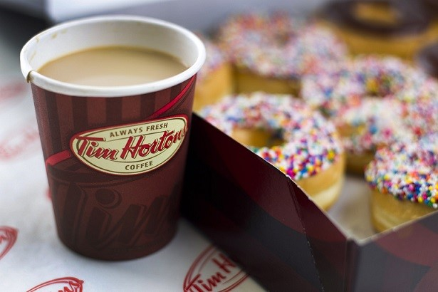 A cup of Tim Hortons Inc. coffee and doughnuts are arranged for a photograph in Toronto, Ontario, Canada, on Wednesday, Aug. 3, 2011. Tim Hortons Inc. is a chain of franchise fast food restaurants that serve coffee drinks, tea, soups, sandwiches, donuts, bagels, and pastries. Photographer: Brent Lewin/Bloomberg via Getty Images