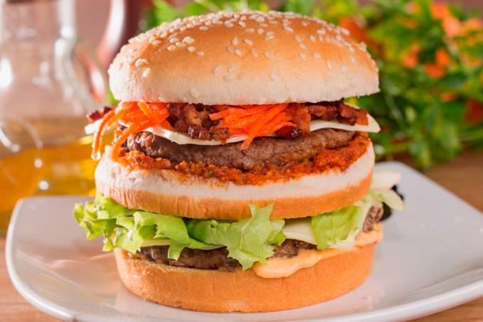 O hambúrguer da culinarista: dois bifes de carne moída, alface-crespa, queijo cheddar branco, molho especial, cebola empanada, picles de cenoura, pesto de tomate seco no pão com gergelim