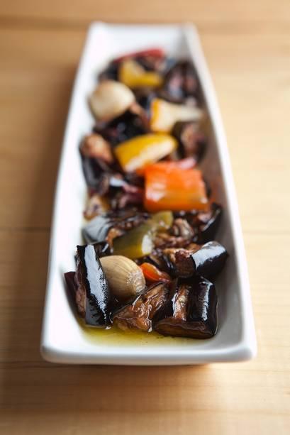 Berinjela frita em pedaços e mergulhada em azeite junto de pimentão, azeitona preta, cogumelo-de-paris e cebolinhas assadas
