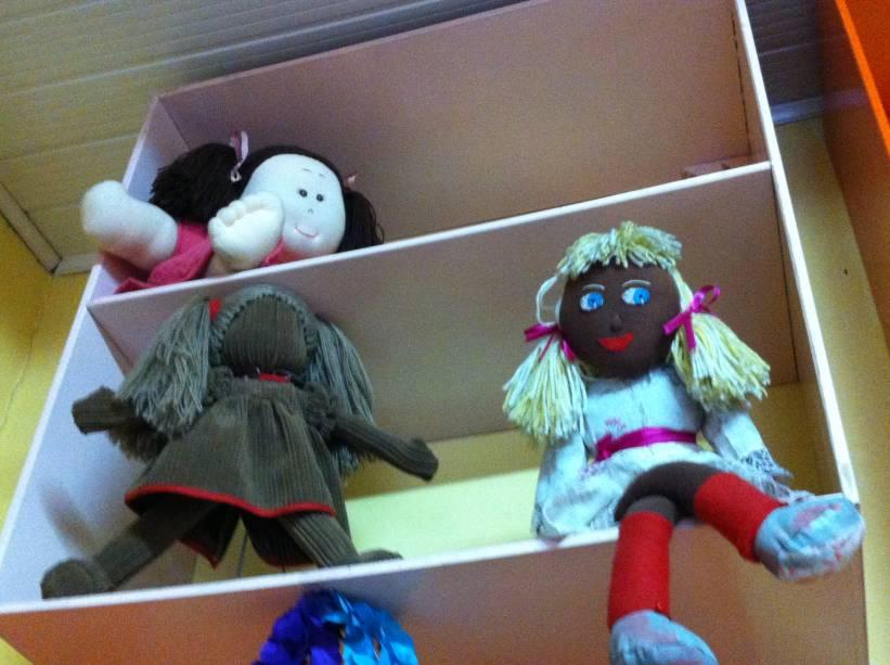 A boneca sem expressão (R$ 89,90) estimula a imaginação da criança. Ao lado, uma negra, com cabelo loiro (R$ 75,00). Na prateleira acima, uma boneca obesa (R$ 160,00)