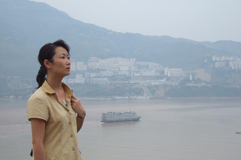 Mulher na frente de um rio com expressão séria