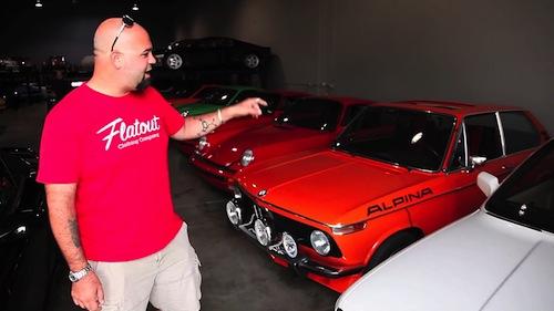 O apresentador circula pelo galpão onde estão os carros de Paul Walker