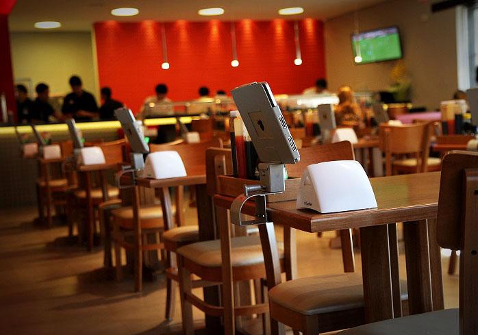 Mesas com iPad para visualizar o cardápio e fazer o pedido
