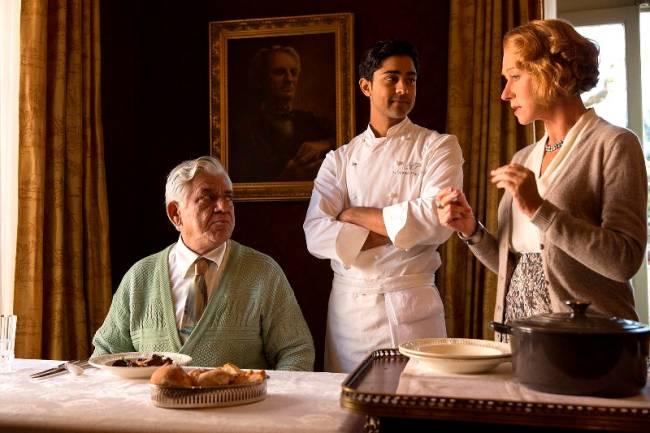 Três pessoas à mesa: senhor sentado à esquerda, homem com vestes de chef de cozinha em pé olhando para senhora à direita em pé.