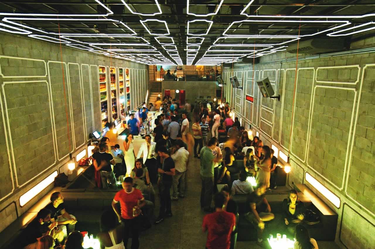 Espaço de um bar visto de cima, com néons no teto