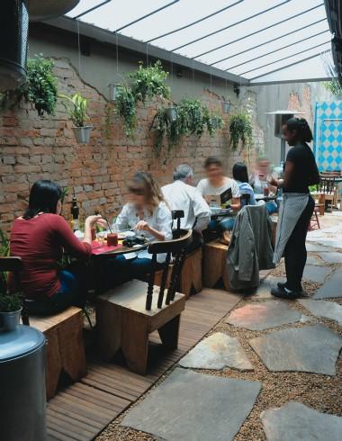 MEsas em jardim com atendente em pé e clientes sentados