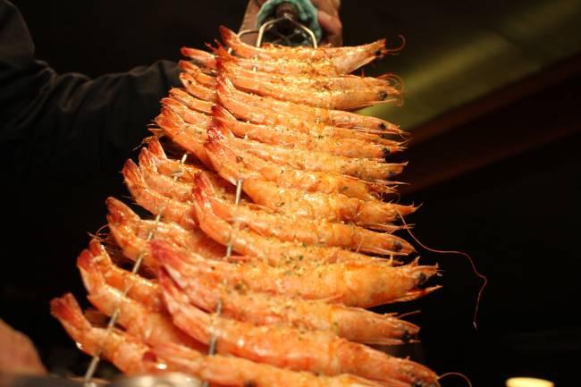 Assados no espeto: os camarões grandes são servidos no festival