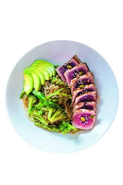 Atum levemente grelhado ao lado de macarrão oriental de feijão-verde, vegetais e abacate