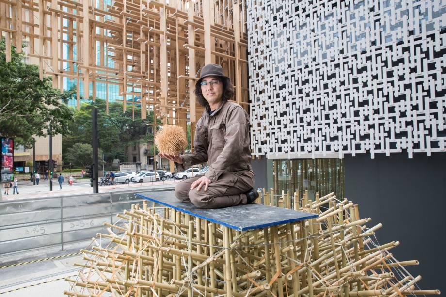 Akio Hizume senta na instalação que construiu especialmente para a mostra