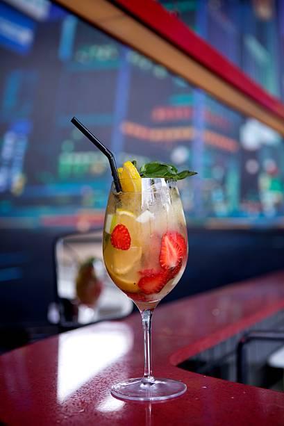 """<strong>Le Boe Ibérico</strong> - O finalista Gustavo Guedes, 30 anos, criou estareceita à base de gin <b>Tanqueray Ten</b> e espumante. """"O nome do drink é uma homenagem ao médico anatomista Franz De Le Boe, considerado o inventor do gin. Esse coquetel é refrescante, aromático e, ainda por cima, pode ser feito em jarra para receber os amigos"""", diz. Receita: 60ml de gin Tanqueray Ten; 60 ml de espumante brut; 25 ml de Cointreau; 25 ml de suco de laranja; meio pêssego em calda; 3 morangos em fatias; 1/3 de maçã verde em cubinhos; 2 rodelas de laranja; 1 ramo de manjericão. Modo de preparo: Adicionar as frutas e o manjericão em uma taça de vinho tinto.Acrescente o Tanqueray Ten, o Cointreau e o suco de laranja. Mexa com uma colher, misturando os líquidos com as frutas. Acrescente gelo e complete com espumante. Mexa mais um pouco.Para fazer uma jarra, basta multiplicar as quantidades por 4. Dica de mestre: """"lembre-se sempre de colocar muito gelo: quanto mais gelada a bebida, menor será a diluição"""", afirma.(graduação alcoólica 31,40%)"""