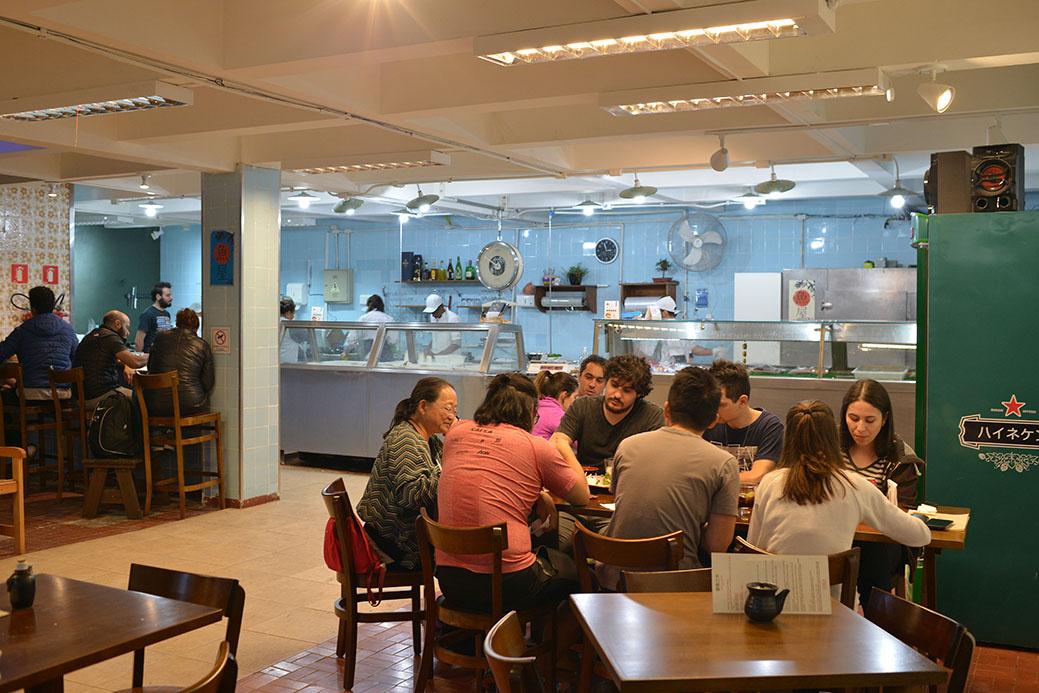 Espaço de peixaria com mesas em frente, montadas como um restaurante