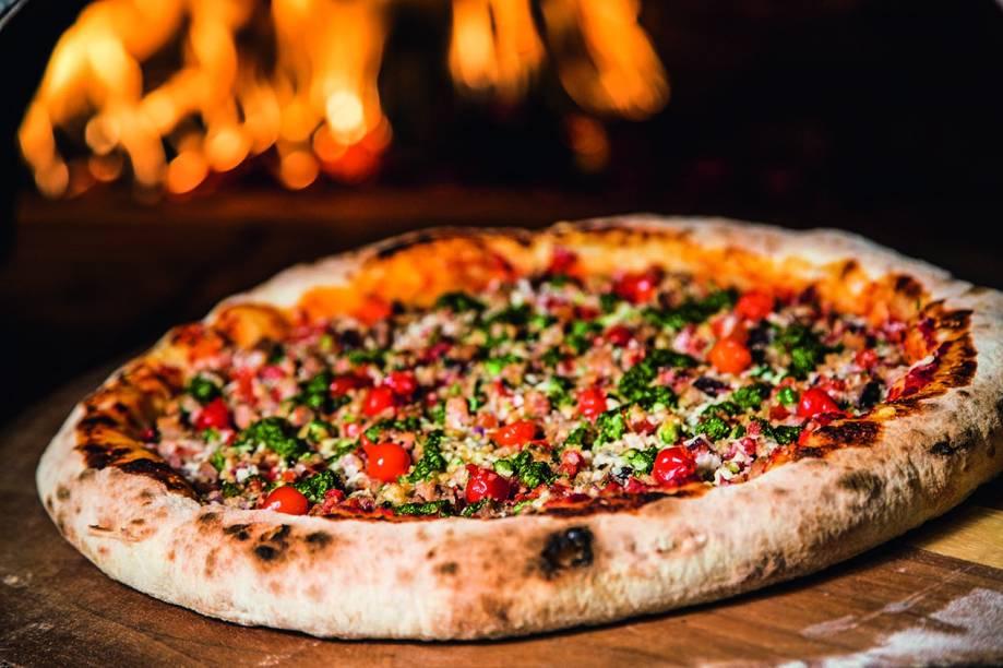 Pizza de carne de sol com manteiga de garrafa leva ainda queijos branco e de coalho, pimentas dedo-de-moça e cambuci, tomate e cebolinha