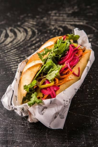 O lanche vietnamita traz na baguete frango levemente agridoce, cenoura, maionese de shoyu, coentro, pimenta jalapeño e picles