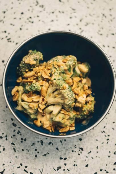 Brócolis cozidos: hortaliça vem com molho de pimenta gochugaru e amendoim com a semente salpicada
