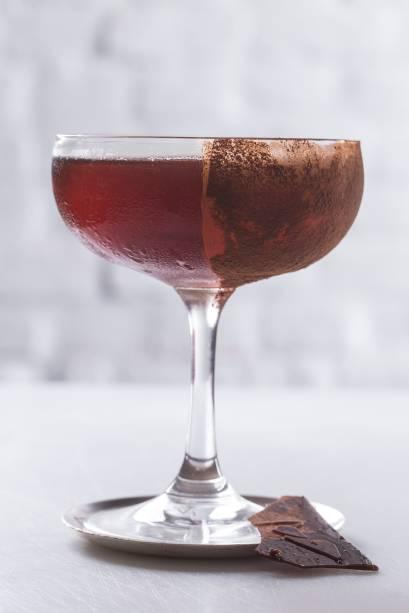 Manhattan chocolat: releitura do clássico com bourbon, leva vermute com infusão de cacau e bitter de notas torradas, servido na taça polvilhada de cacau