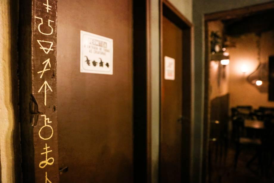Detalhe na porta dos banheiros, símbolos místicos decoram o ambiente